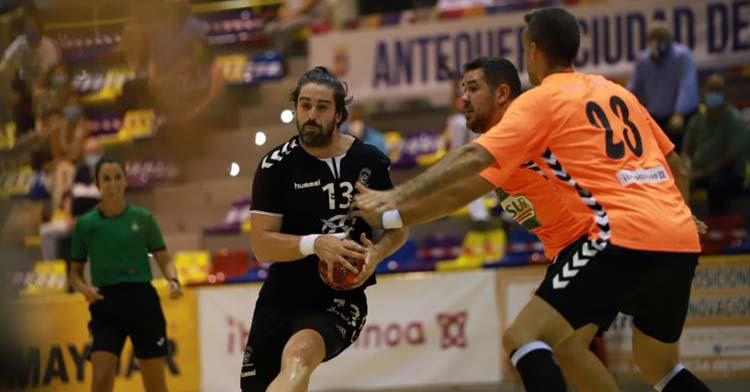 Vicente Poveda intenta penetrar ante dos jugadores de Antequera.