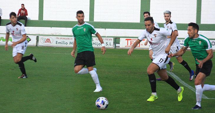 Carlos Valverde busca el balón ante un jugador del Pozoblanco con Willy al fondo.