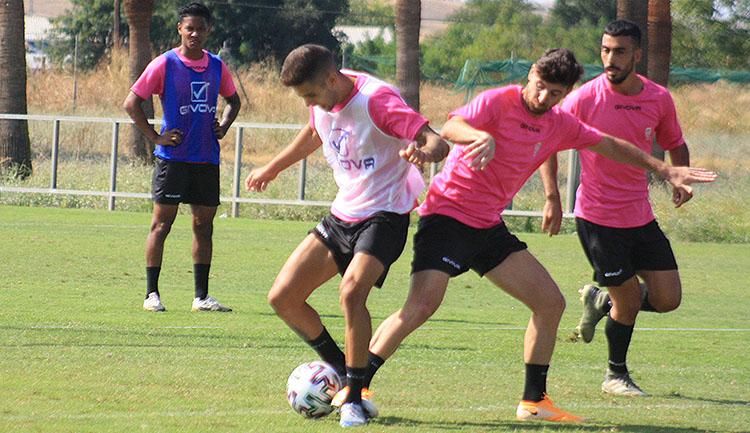 Julio Iglesias llevándose el balón ante Javi Flores, con Antonio Moyano al fondo.
