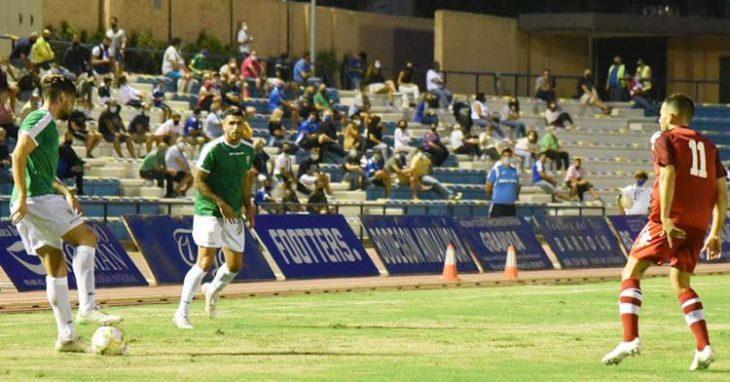 Samu Delgado pisa el balón bajo la mirada de Álex Robles con el público de San Fernando de vuelta al Bahía Sur.