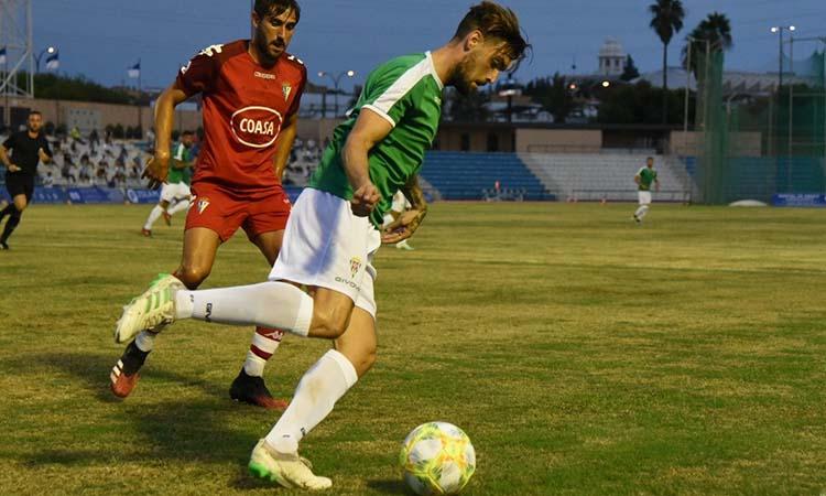 Samu Delgado protege el balón ante la llegada de un jugador del San Fernando.