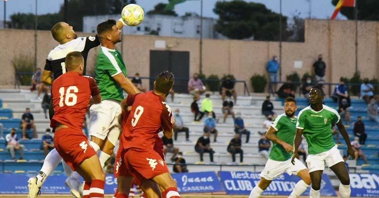 El meta del San Fernando Perales se adelanta a Willy para despejar con su puño.