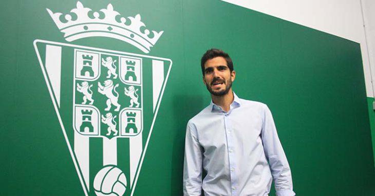 Bernardo Cruz posando junto al escudo del Córdoba CF.