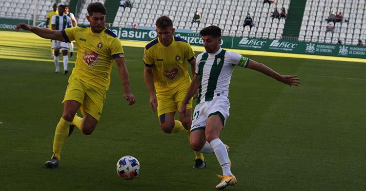 Javi Flores controla el balón ante la llegada de dos jugadores del Lorca.