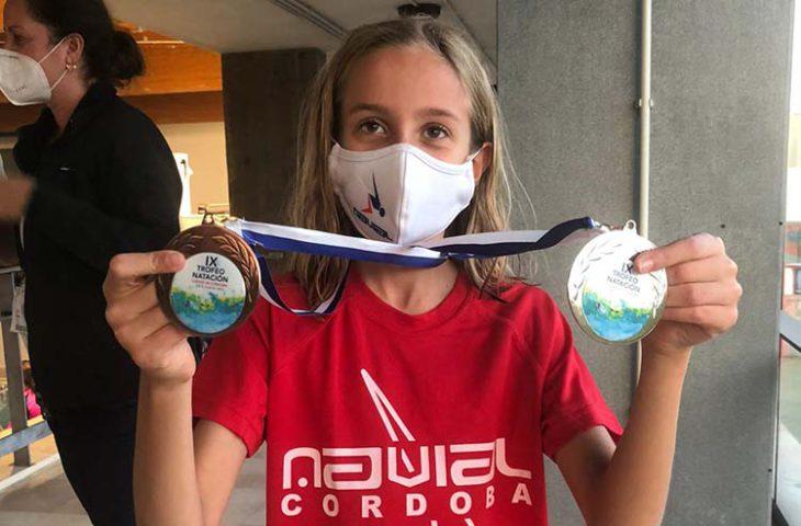 La joven Candela González muestra sus dos preseas que sumaron para el medallero de Navial.