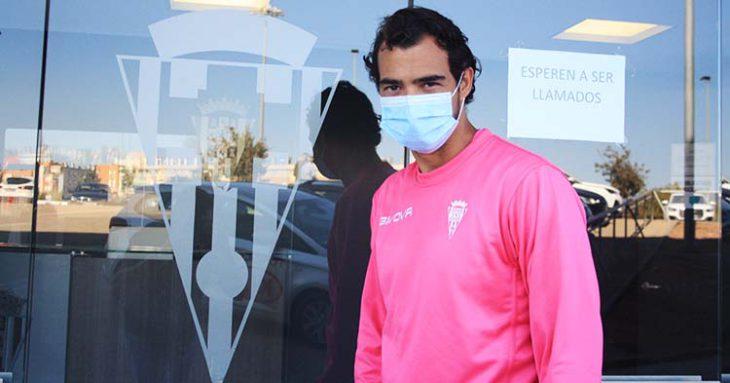 Miguel de las Cuevas posando junto al escudo del Córdoba con su mascarilla de la nueva normalidad.