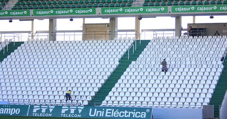 Las operarias del Córdoba señalizando los asientos de la grada de Fondo Sur con la distancia de seguridad reglamentaria de cara al debut liguero ante el Lorca.