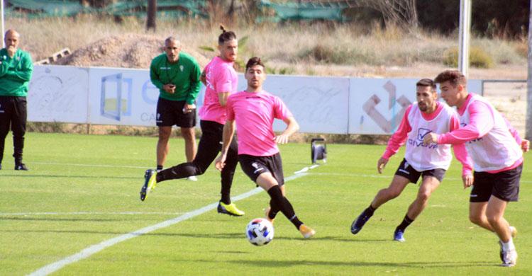 Alberto Del Moral busca el balón ante Javi Flores, con Samu Delgado y Carlos Valverde en segundo plano, mientras Manu Robles y Sabas siguen el entrenamiento al fondo.