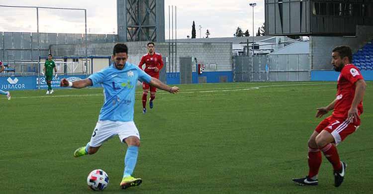 Un jugador del Ciudad de Lucena desplaza el balón en largo ante la llegada de un contrario del Utrera.