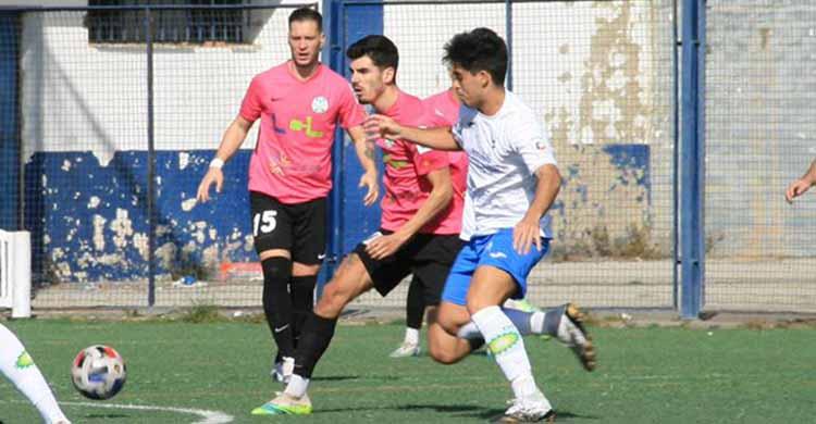 Un futbolista del Ciudad de Lucena se adelanta a un jugador del Castilleja.
