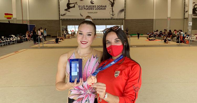 Sonia Ortiz posa con su medalla y el trofeo correspondiente junto a su entrenadora