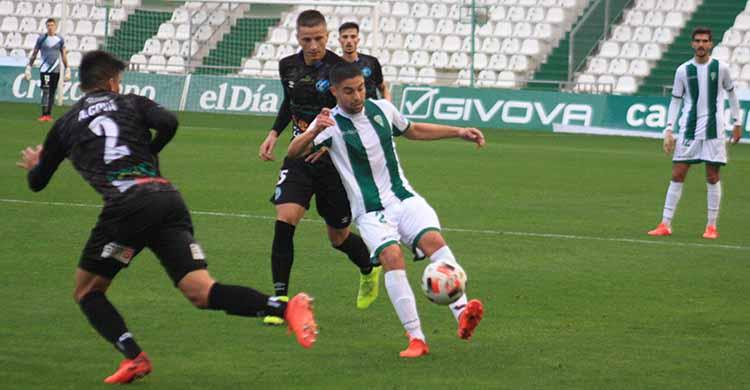 Jesús Álvaro pasa el balón entre dos jugadores de El Ejido.
