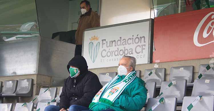 El cartel de la Fundación con un par de cordobesistas en la grada en el partido ante el Getafe, el último que permitió asistencia de público a El Arcángel