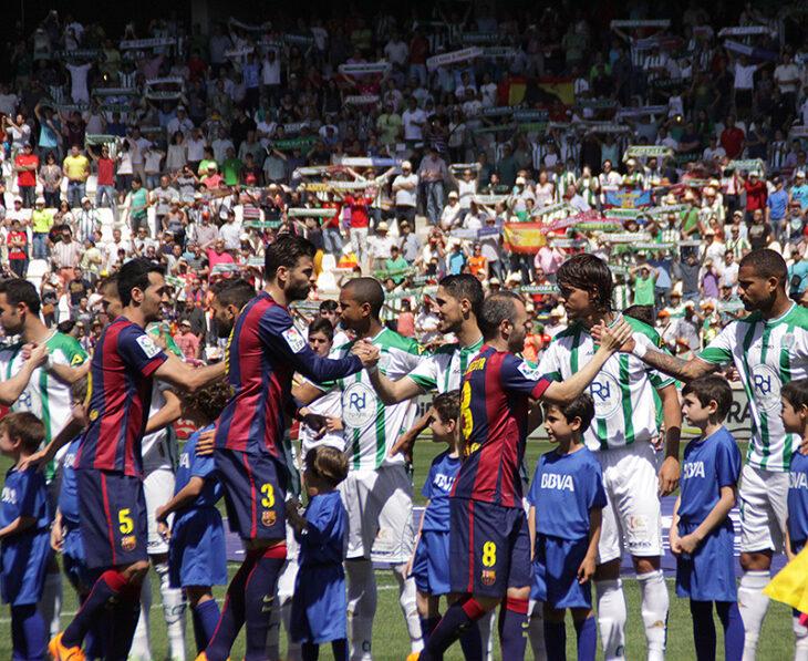 Busquets, Piqué y Andrés Iniesta saludando a Edimar, Fidel y Khrin con el cordobesismo al fondo luciendo sus bufandas.