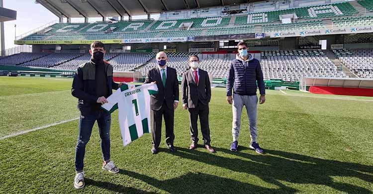 Javi Flores y Bernardo Cruz muestran la camiseta con el patrocinio de La Caixa ante el director territorial de Andalucía Oriental y Javier González Calvo.