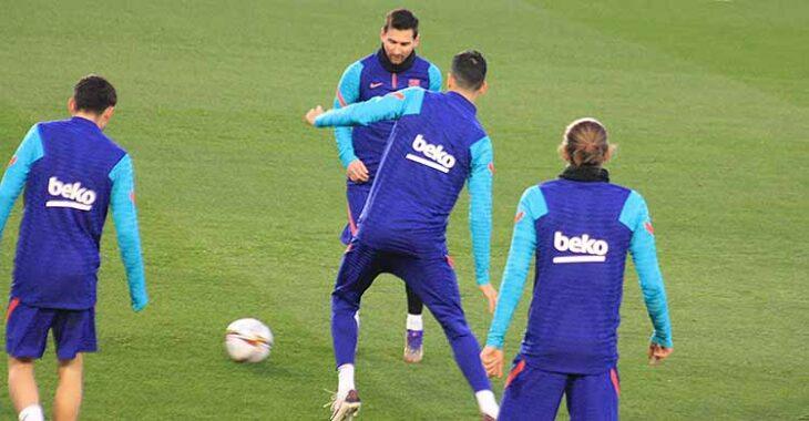 Messi pasa el balón ante la llegada de Sergio Busquets.