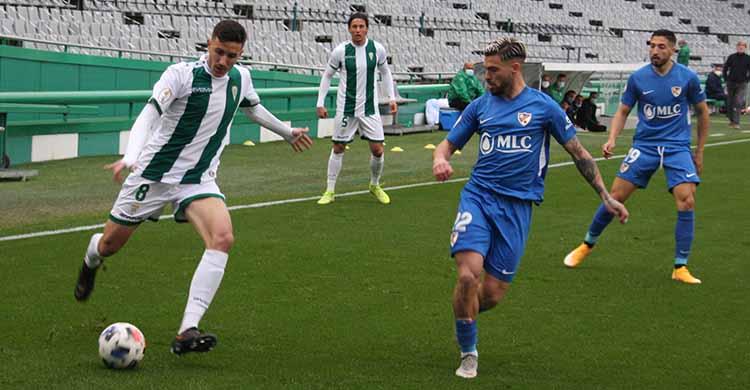 Alberto Ródenas busca el centro ante un jugador el Linares.