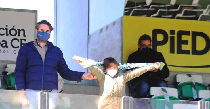 Un joven cordobesista mostrando la bufanda del Córdoba CF junto a su padre.