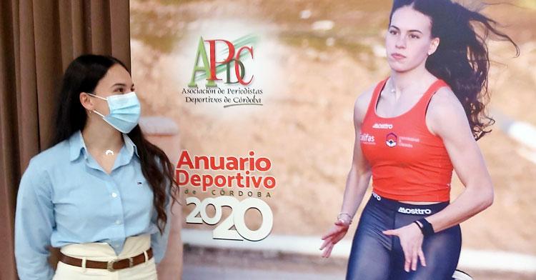 Carmen Avilés mirando al póster que emula la portada del Anuario 2020, con ella como protagonista