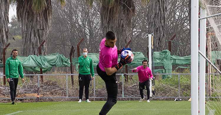 Edu Frías tras atrapar un balón aéreo, con Miguel de las Cuevas al fondo trabajando la recuperación con Javi Poveda.