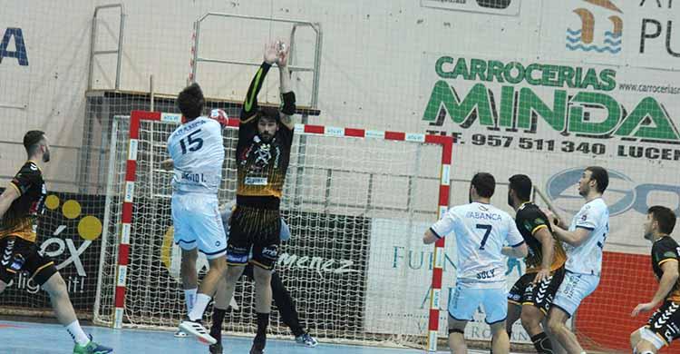 Javi García intenta blocar un lanzamiento de un jugador del Cangas.