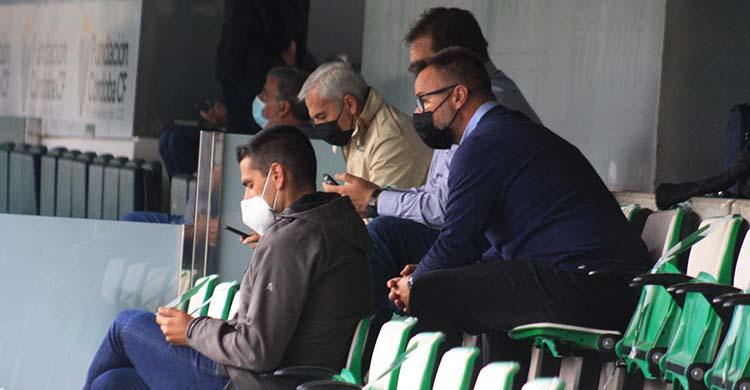 Juanito en primer plano con el nuevo técnico del filial, David Ortega, a sus espaldas, con Rafa Herrerías y Miguel Valenzuela al fondo igualmente centrados en sus móviles.
