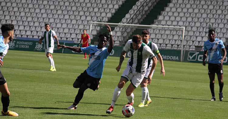 Nahuel Arroyo dejando atrás a un jugador del Linense con Javi Flores al fondo.