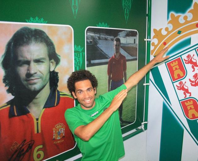 Quim Araujo posando con la imagen de Paco Jémez y Rafa Berges de fondo con la enseña nacional.