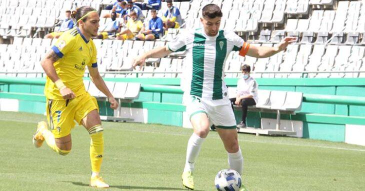 Javi Flores protege el balón ante la llegada de un jugador del Cádiz B