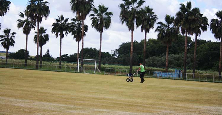 Un operario trabajando sobre el campo primero de la Ciudad Deportiva tras retirarse su césped.