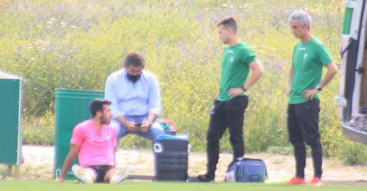 Carlos Puga sentado sobre el césped en la banda ante Javier González Calvo y el doctor Bretones.