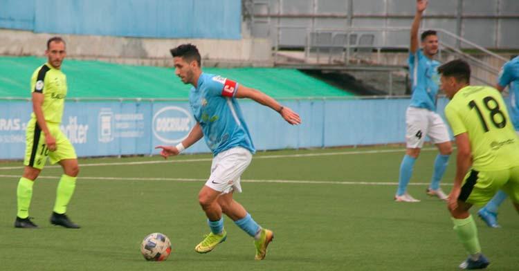 Toni Pérez conduciendo la pelota ante la mirada de dos jugadores del Ceuta. Foto: Ciudad de Lucena.