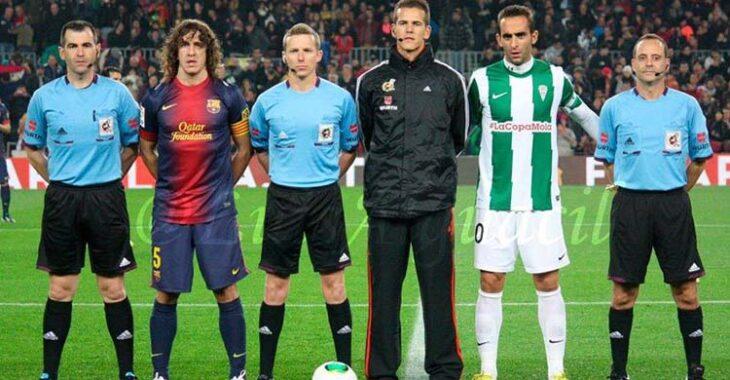 Alberto Aguilar portando el brazalete de capitán del Córdoba CF en el Nou Camp posando con el trío arbitral junto a Puyol.