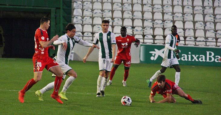 Adrián Fuentes, con el dorsal 20, encimando a Farrando en El Arcángel durante el partido ante el Real Murcia.