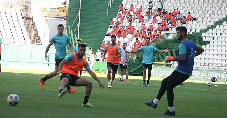 El meta del filial Hankins pasa el balón ante la llegada de Puga, con los niñ@os del Club Mirabueno al fondo en la grada del Fondo Norte.