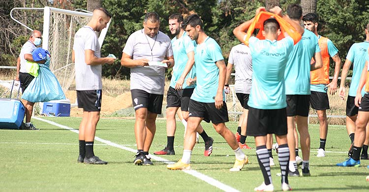 Germán Crespo repasando sus notas junto a Álex Prieto y varios jugadores.