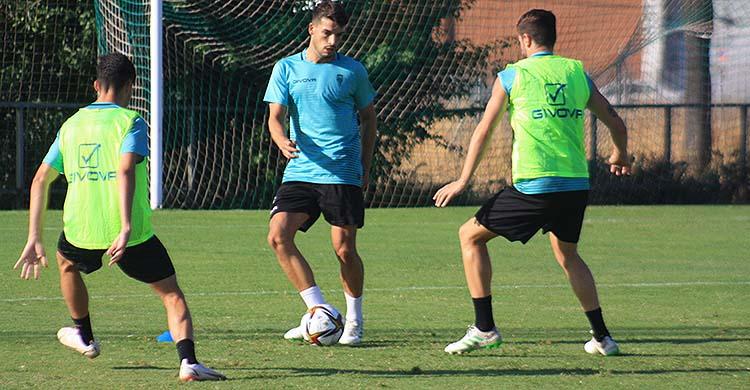 El onubense José Alonso tocando el balón ante la presión de Toni Arranz y Luismi Delgado.