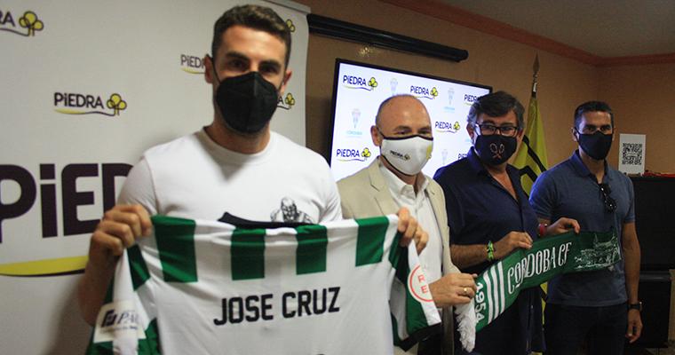 José Cruz mostrando su camiseta en la sede de Piedra durante su presentación acompañado por el director de los supermercados cordobeses junto a Javier González Calvo y Juanito.