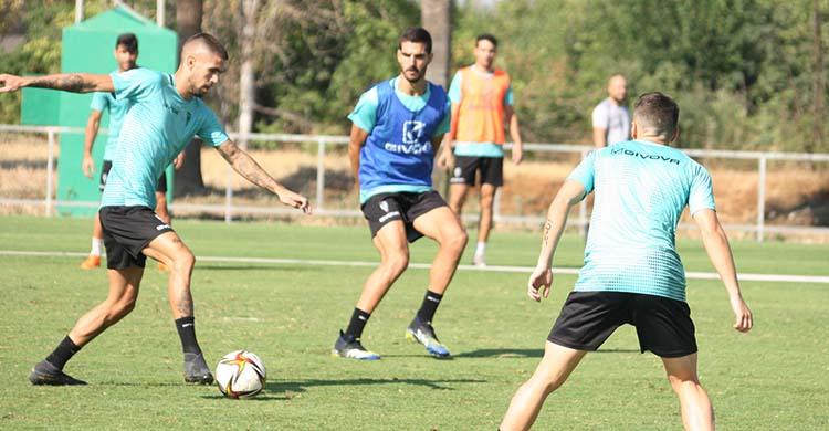 Julio Iglesias avanza con el balón con Bernardo Cruz al fondo.